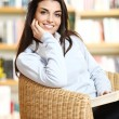 Stock Photo: Smiling female student with book in hands sitting in a chair in