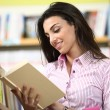 Stock Photo: Smiling female student reading a book in a bookstore