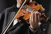 The violinist: Musician playing violin on dark background — Stock Photo