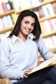 Estudiante sonriente con el libro en las manos en una librería - modelo — Foto de Stock