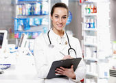 At pharmacy. A smiling young woman pharmacist wearing stethosco — Stock Photo