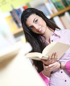 Smiling female student with book in hands in a bookstore - model — Stock Photo