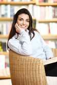 Smiling female student with book in hands sitting in a chair in — Stock Photo