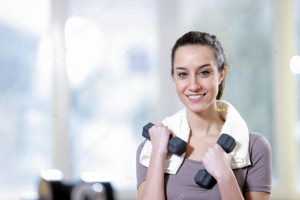 Dumbbell in hand of working out young smiling female — Stock Photo #9034866