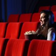 A pretty young woman sitting in an empty theater, she eats popco — Stock Photo #9058500