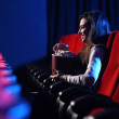 Funny movie: portrait of a pretty young woman, eats popcorn and — Stock Photo #9058514