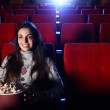 A pretty girl alone sitting in a empty movie theater, she eats p — Stock Photo #9058563