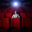 Beautiful young woman alone sitting in a empty movie theater — Stock Photo #9058578