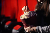 Close up of the hands of a girl in a movie theater, she eats pop — Stock Photo