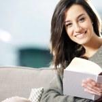 retrato de uma jovem feliz, deitado no sofá com o livro — Foto Stock