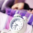 An alarm clock with a sleeping young woman in the background — Stock Photo #9192983