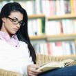Female student reading a book in library — Stock Photo