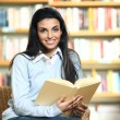 Smiling female student with book in hands sitting in a chair in — Stock Photo #9203291