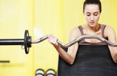 Gym: portrait of young woman lifting weights — Stock Photo