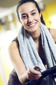 A young woman riding an exercise bike — Stock Photo