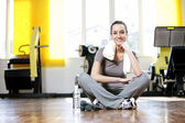 Young woman sitting on the gym's floor after workout — ストック写真