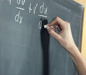 Close-up of a stunden's hand solving maths problem — Stockfoto