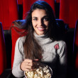 A pretty young woman sitting in an empty theater, she eats popco — Stock Photo