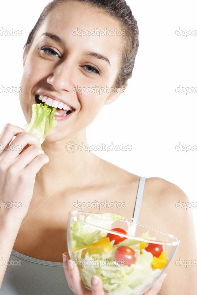 Woman eating salad. Portrait of beautiful smiling and happy woman enjoying a healthy salad and cherry tomatoes — Stock Photo #9290266