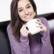 Beautiful young woman having coffee while at the kitchen — Stock Photo #9340047