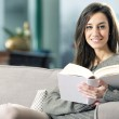Portrait of a happy young woman lying on couch with book — Stock Photo