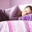 Close-up of an attractive young female sleeping in bed at home — Stock Photo #9340359