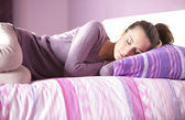 Close-up of an attractive young female sleeping in bed at home — Stock Photo