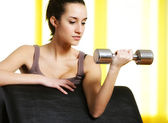 Portrait of young woman lifting free weights — Stock Photo