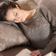 Woman lying on couch with book — Stock Photo
