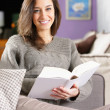 Young woman lying on couch with book — Stock Photo