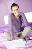 Woman in bed while using laptop — Stock Photo