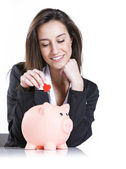 Close-up of young woman putting a red hearth into a piggy bank, — Foto de Stock
