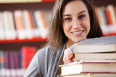 Smiling college student with a stack of books — Stock Photo