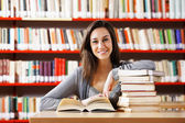 Portrait of a student girl studying at library — Stok fotoğraf