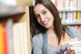 Student with pile of books in the Library — Stock Photo