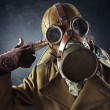 Grunge portrait man in gas mask pointing hand gun at his own hea — Stock Photo