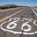 largo camino con un inicio de sesión de ruta 66 pintado — Foto de Stock   #9581006
