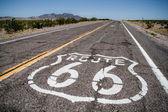 Lunga strada con un accesso di route 66 dipinte su di esso — Foto Stock