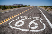 Long road with a Route 66 logon painted on it — Stock Photo