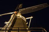 Night view of traditional Dutch wooden illuminated corn-mill — Stock Photo