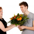 Young man gives his girlfriend a large bouquet of flowers — Stock Photo