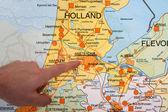 A Dutch map with a hand pointing to the capital city Amsterdam — Stock Photo