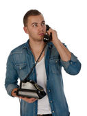 Young man making a phone call with an old telephone against a wh — Stock Photo