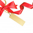 Beautiful ribbon with red bow and a label isolated on white background — Stock Photo