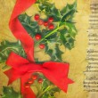 Christmas card with holly and red bow - Stok fotoğraf