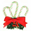 Royalty-Free Stock Photo: Three candy canes tied with a red ribbon and with a holly sprig.