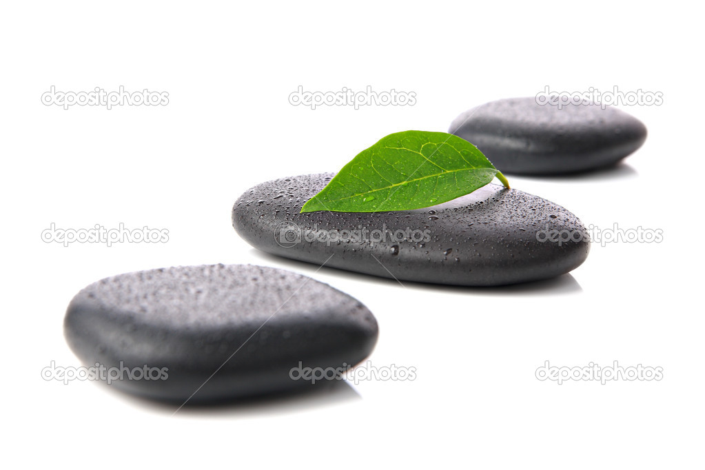 Three wet hot stones with a green leaf on a white background — Stock Photo #7980899