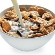 Milk poured into bowl of bran cereal - Stock Photo