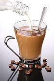 Milk poured into coffee — Stock Photo