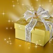 Golden gift box or present with ribbon and bow — Stock Photo